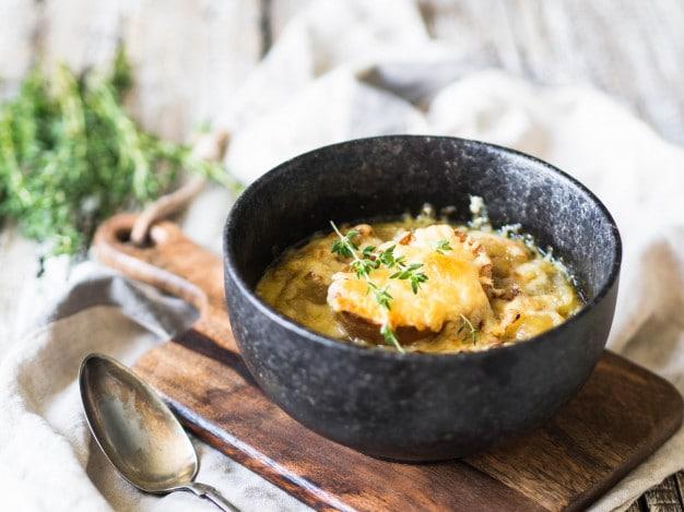 traditionele-franse-uiensoep-met-toast-kaas-en-verse-tijm-in-een-zwarte-kom_86156-17